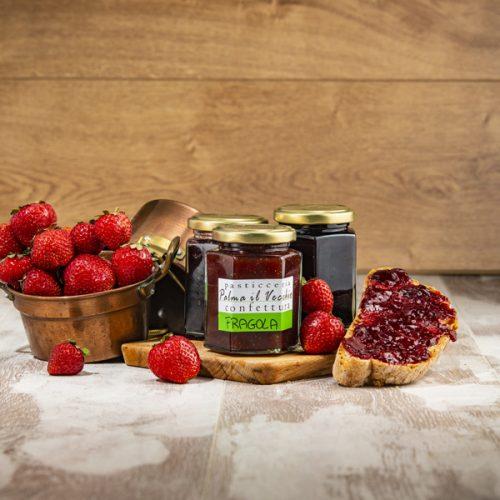 Presentazione del prodotto composta da barattoli di Confettura di Fragola, pane spalmato e fragole fresche contenute in pentolini di rame.