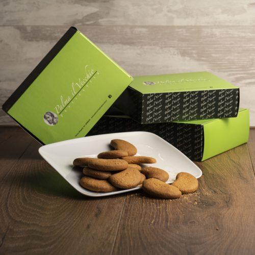 Presentazione del prodotto composta da confezioni di Biscotti Mezzelune e una manciata di biscotti presentati su di un piatto bianco.