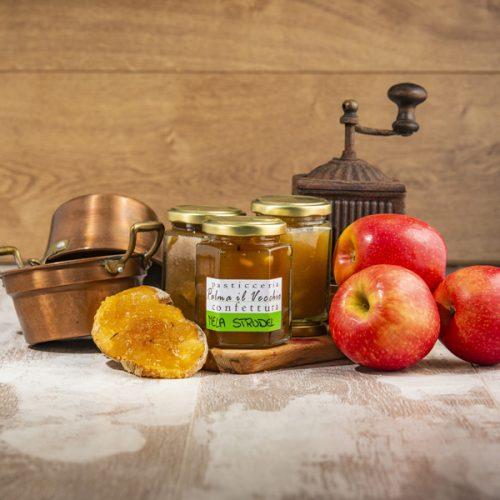 Presentazione del prodotto composta da barattoli di Confettura Mela Strudel, fette di pane spalmato, mele, pentolino di rame e macinino.