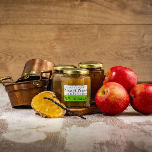 Presentazione del prodotto composta da barattoli di Confettura Mela e Vaniglia, mele, una bacca di vaniglia e pentolini di rame.
