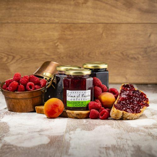 Presentazione del prodotto composta da confezioni di Confettura Albicocca e Lampone, pane spalmato e frutta fresca.