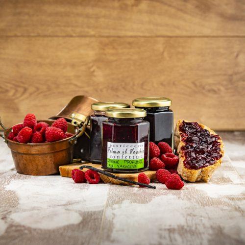 Presentazione del prodotto composta da confezioni di Confettura Lampone e Vaniglia, pane spalmato e frutta fresca.