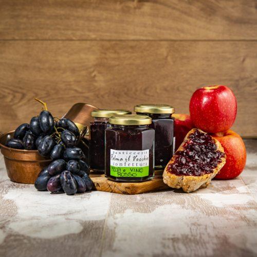Presentazione del prodotto composta da barattoli di Confettura Mela e vino rosso, pane spalmato, mele e uva fresche contenute in pentolini di rame