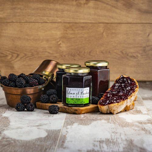 Presentazione del prodotto composta da barattoli di Confettura Mora Selvatica, pane spalmato e frutta fresca dentro pentolini di rame.
